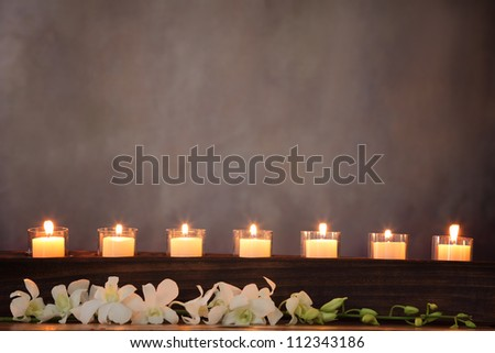 Row of burning candles with white orchid flower,zen concept.