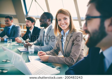 Row of business people listening to presentation at seminar with focus on smiling woman looking at camera