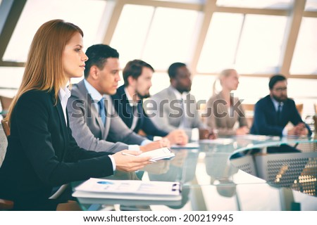 Row of business people listening to presentation at seminar with serious woman on foreground