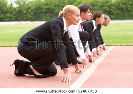 Row of business people looking attentively forwards before signal to run