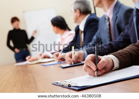 Row of business people making notes during presentation