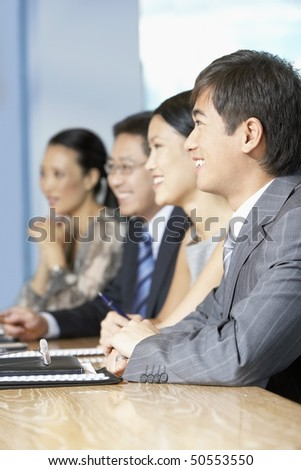 Row of business people sitting at table in conference room