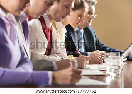 Row of businesspeople writing review of their work with senior boss at background