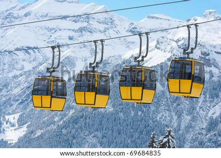 Row of cablecars against snowy swiss alps. January 2011. Switzerland
