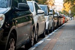 row of cars parked near the sidewalk