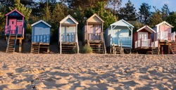 Row of characterful, colourful beach huts on the sea front at Wells-next-the-Sea, North Norfolk UK. The huts are photographed in the late afternoon at golden hour. Sand in the foreground.