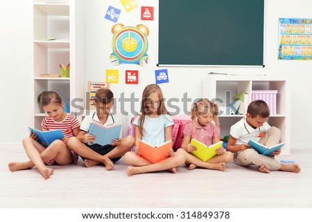 Row of children reading on floor in classroom