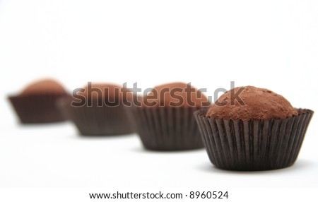 Row of chocolate truffles against a white background.