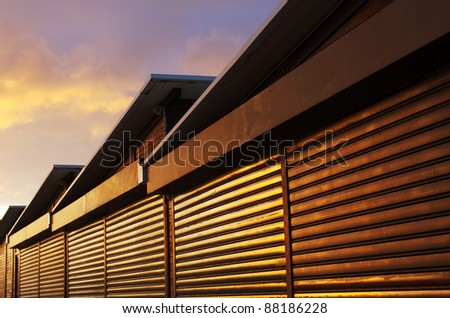 Row of closed storage cabins with stripped wooden walls under warm sunset light