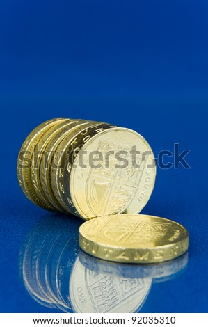 Row of coins with reflection isolated on blue background / Row of pound coins