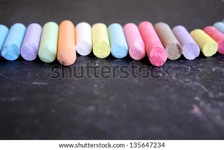 Row of colored chalk on blackboard