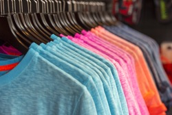Row of colored t-shirts in a store