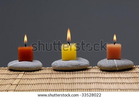 Row of colorful alight candle on zen stones