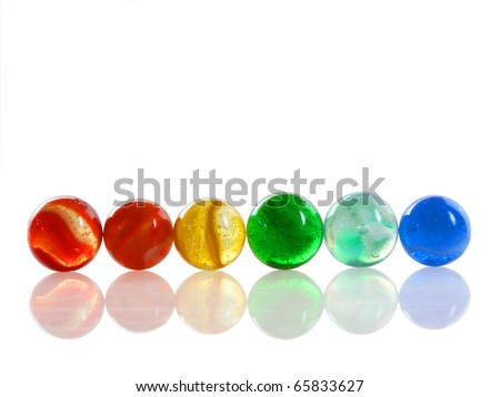 Row of 6 colorful antique marbles on a reflective white surface
