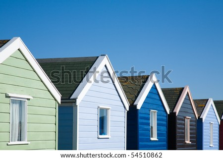 row of colorful beach huts under blue sky