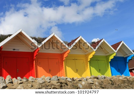 Row of colorful beach huts with blue sky and cloudscape background, summer beach scene.