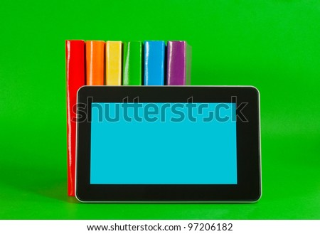 Row of colorful books and tablet PC over green background