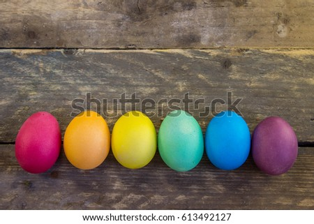 Row of colorful easter eggs on wooden desks . - Shutterstock ID 613492127
