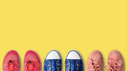 Row of colorful female summer shoes collection yellow background close up top view, women fashion sneakers set, stylish gumshoes, sport and casual walking footwear, shoe shop, store sale, copy space