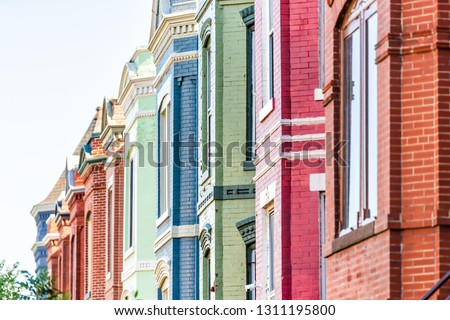 Row of colorful red green and blue painted brick residential townhouses homes houses architecture exterior in Washington DC Capitol Hill neighborhood district
