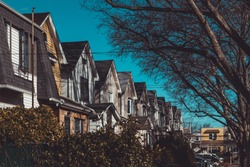 Row of colorful residential houses in Queens, NY on clear, sunny day