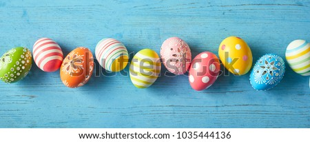 Row of colorfully painted Easter eggs on blue wooden background, wide angled image. #1035444136