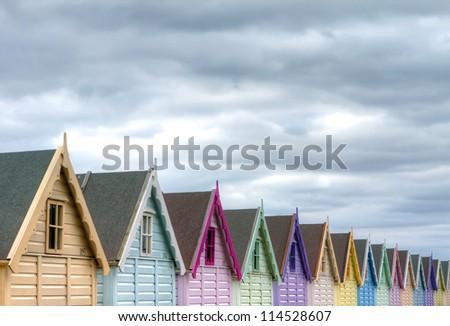 row of coloured beach huts on a gloomy day