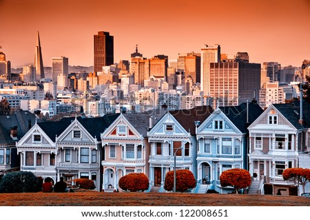 Row of colourful Victorian homes on Steiner Street with the San Francisco skyline behind.