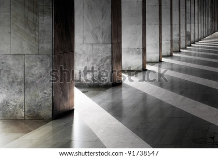 Row of columns with sunlight in the gaps and reflected in shiny floor #91738547