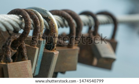 Row of corroded, rusty love locks / padlocks attached to bridge in Portugal. Close up / macro with shallow depth of field. #1474540799