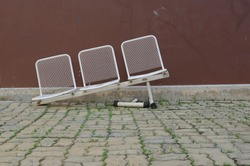 Row of damaged white metal chairs with broken leg, slanted chairs are abandoned on paving stone in the park