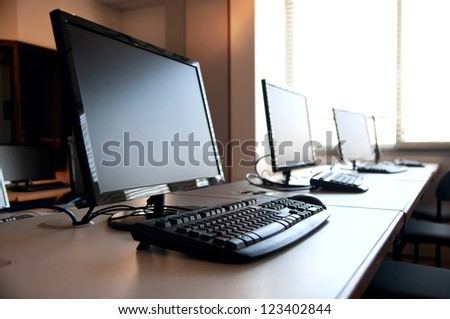 Row of desktop PCs workplaces in the classroom