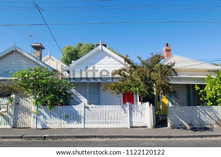 Row of detached bungalow homes in the residential suburb of St Kilda in Melbourne with a white picket fence and a blue sky background. Power cables overhead.