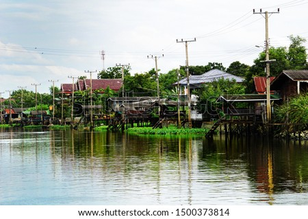 Row of Electric poles. Electrical pole in waterfront community. Water reflection of row of electric poles and houses.