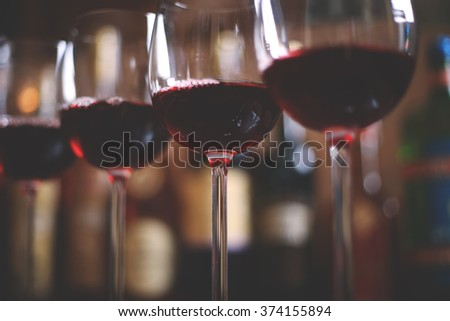 Row of elegant wine glasses with red wine on the bar on the background of a row of alcohol bottles.