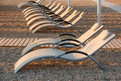 row of empty sun loungers on the shore are empty in the absence of tourists. Concept of no tourists during the coronavirus pandemic, COVID-19