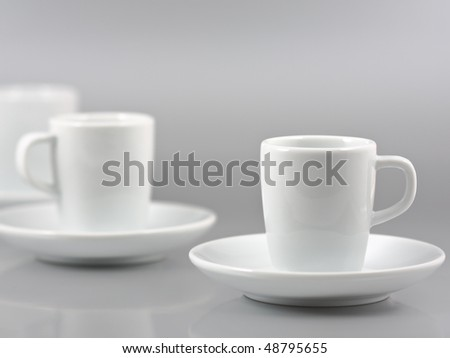 Row of espresso cups on silver background