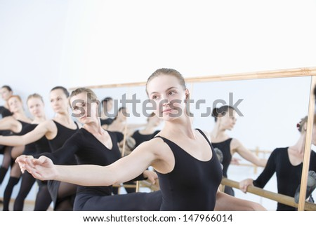 Row of female ballet dancers practicing at barre in rehearsal room