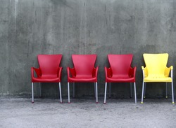 Row of four chairs. Three red, one yellow.