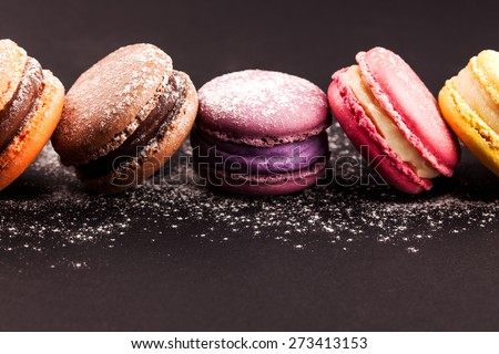 Row of french colorful macaroons with powdered sugar, lying on black background