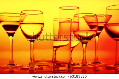 row of glass glasses with refractions and reflections on an equal surface in yellow orange warm lighting