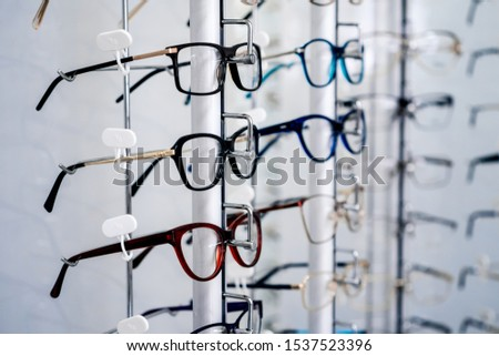 Row of glasses at an opticians. Eyeglasses shop. Stand with glasses in the store of optics. Eyesight correction.