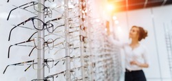 Row of glasses at an opticians. Eyeglasses shop. Stand with glasses in the store of optics. Woman chooses glasses. Presenting spectacles