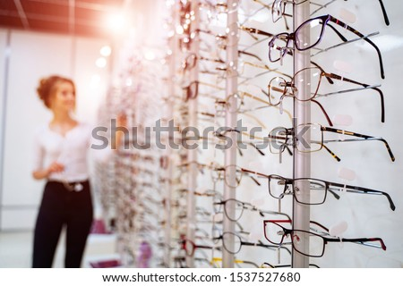 Row of glasses at an opticians. Eyeglasses shop. Stand with glasses in the store of optics. Woman chooses spectacles. Eyesight correction.