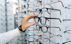 Row of glasses at an opticians. Eyeglasses shop. Stand with glasses in the store of optics. Woman's hand chooses spectacles. Eyesight correction.