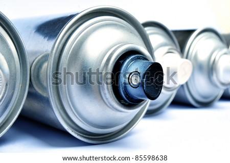 Row of graffiti aerosol cans - Blue toned