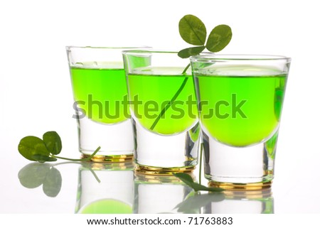 Row of green liquor shots for St Patrick's Day and clover leafs.