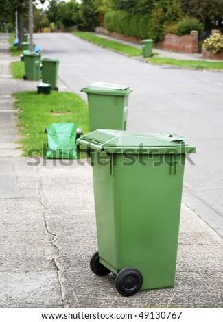 Row of green recycling bins in urban street