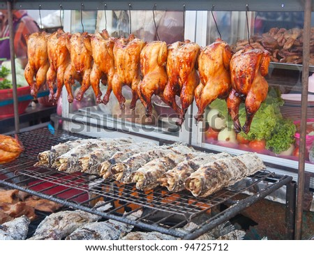 Row of grilled fish and hens on the street market in Bangkok, Thailand