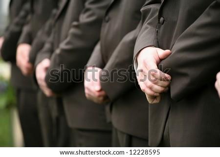 Row of groomsmen's hands at wedding ceremony